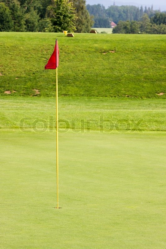 Green golf course with hole and flag, stock photo