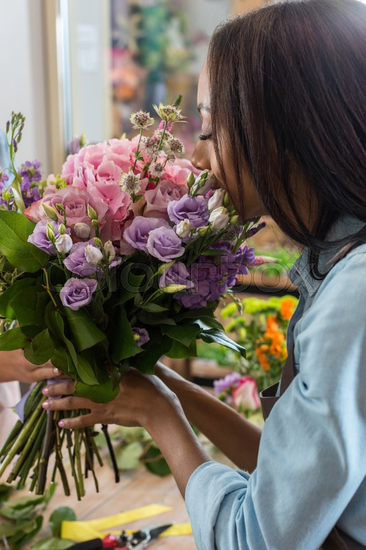 Young african american woman smelling beautiful flowers in flower shop , stock photo