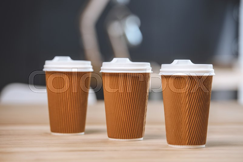 Selective focus of disposable cups of coffee on wooden table, stock photo