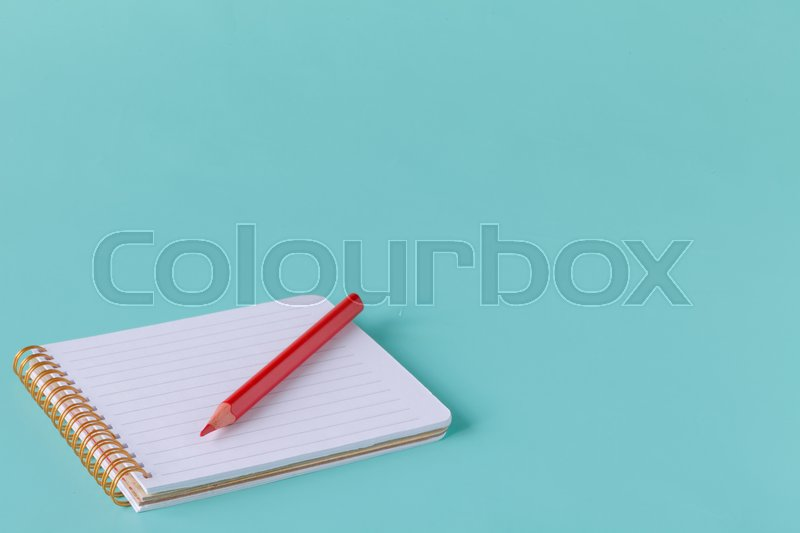 Open spiral blank notebook with pencil on blue paper background, stock photo