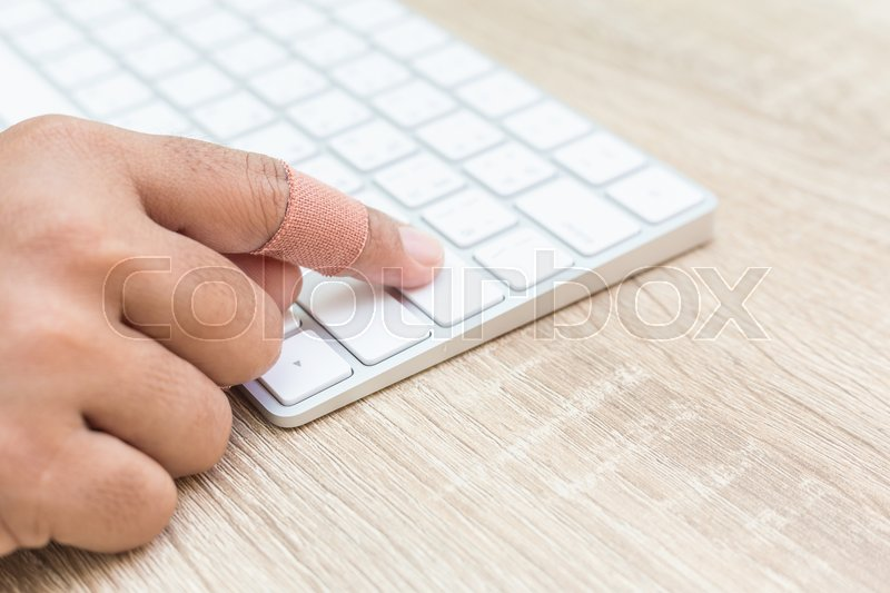 Close up hand with injury on finger using white computer keyboard on wooden background, stock photo