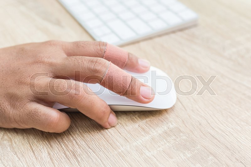 Close up hand with injury on finger using white computer wireless mouse on wooden background, stock photo