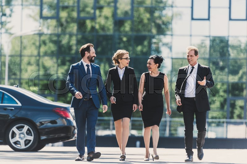 Professional team of middle aged multiethnic businesspeople walking together and talking in city, stock photo