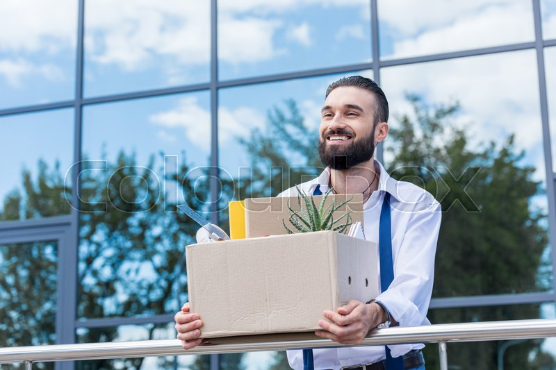 Happy businessman with cardboard box with office supplies in hands standing outside office building, quitting job concept, stock photo