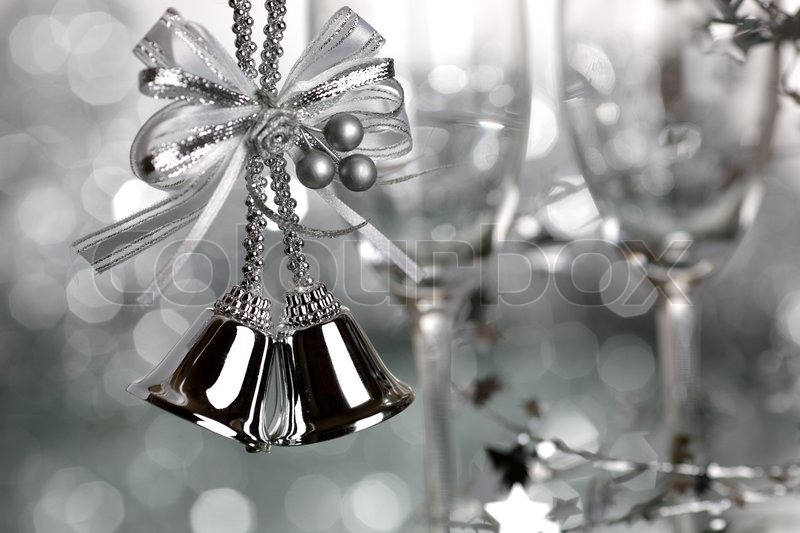 Christmas Bells And Two Empty Wineglass On Silver