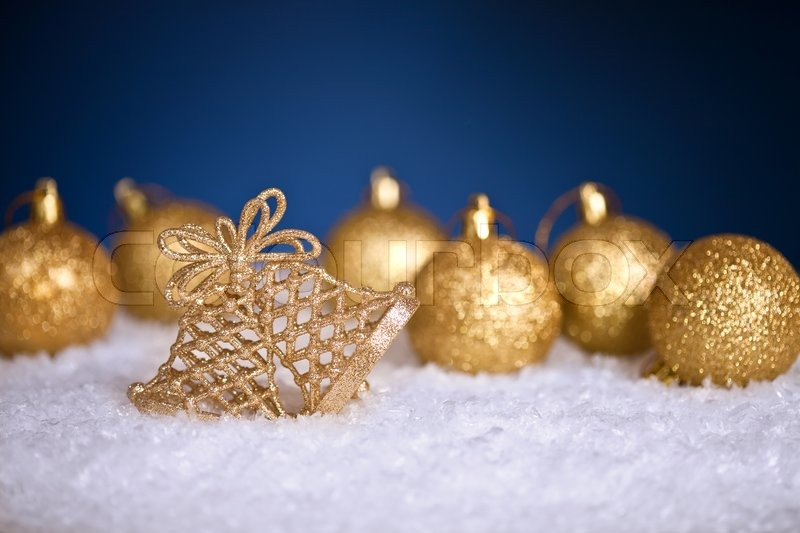 gold christmas tree decorations in snow on blue background stock photo colourbox