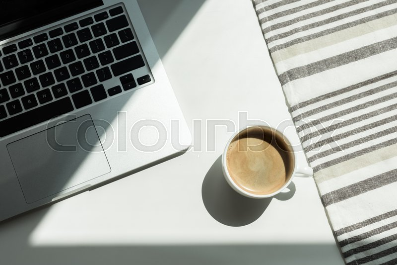 White working desk with laptop computer and cup of black coffee and tablecloth, stock photo