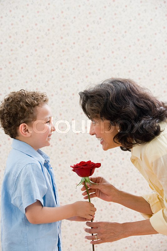 Boy giving rose to grandmother, stock photo