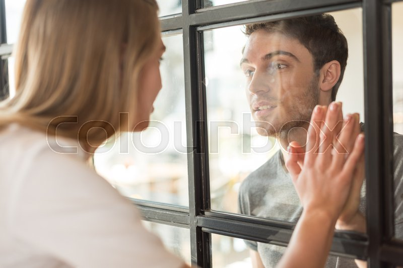 Side View Of Couple In Love Looking At Each Other Through Glass Door