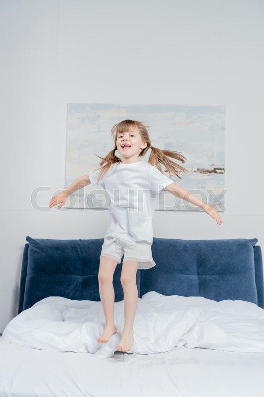 Cheerful girl in pajamas looking at camera while jumping on bed at home, stock photo