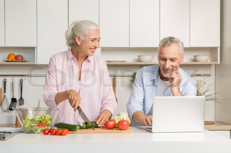 Stock image of 'Picture of mature loving couple family standing at the kitchen using laptop computer and cooking salad. Looking aside.'