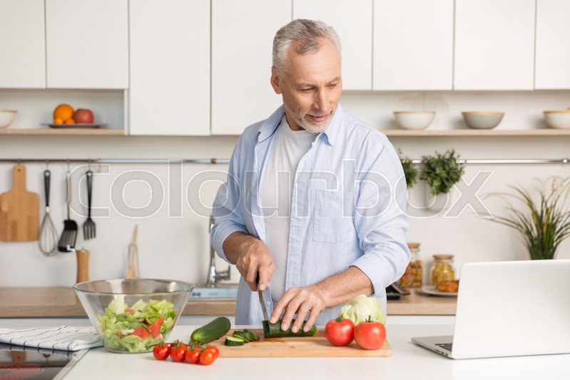 Stock image of 'Picture of mature handsome man standing at the kitchen using laptop computer and cooking salad. Looking aside.'
