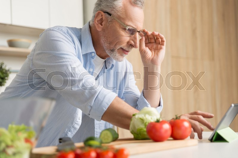 Stock image of 'Picture of handsome mature man wearing glasses standing at the kitchen cooking salad using tablet. Looking aside.'