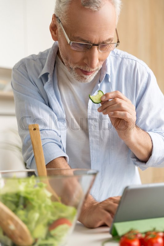Stock image of 'Image of handsome concentrated mature man wearing glasses standing at the kitchen cooking salad using tablet computer. Looking aside.'