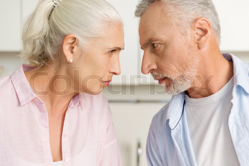 Stock image of 'Image of angry mature man standing near mature serious woman at the kitchen. Looking at each other.'
