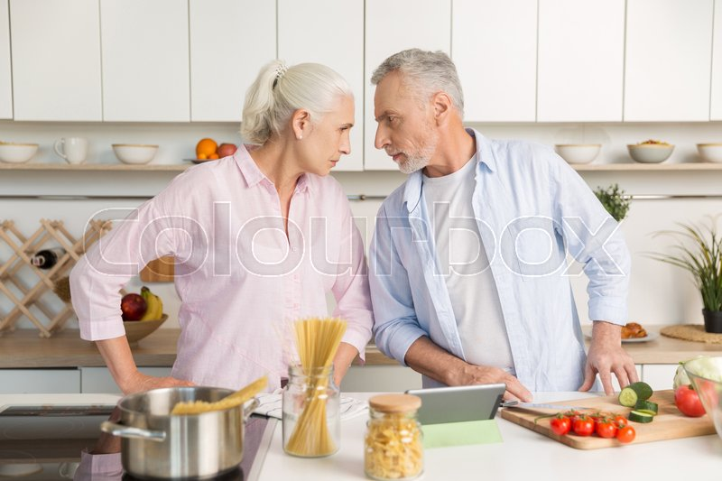 Stock image of 'Picture of angry mature man standing near mature serious woman at the kitchen. Looking at each other.'