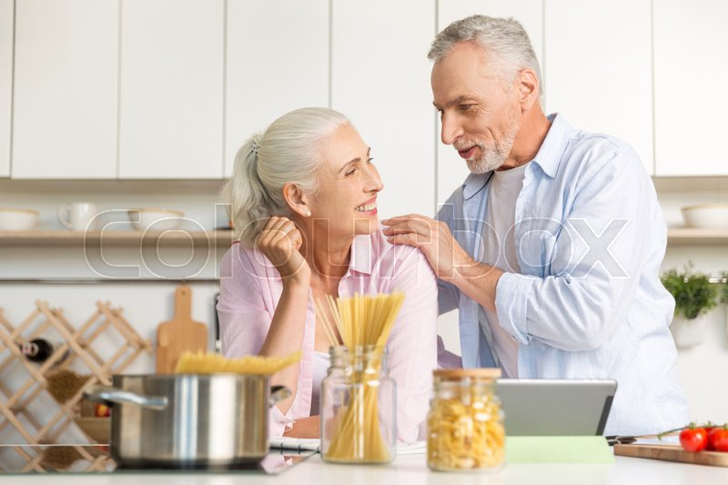 Stock image of 'Image of happy mature man standing near mature cheerful woman at the kitchen cooking at using tablet computer. Looking at each other.'