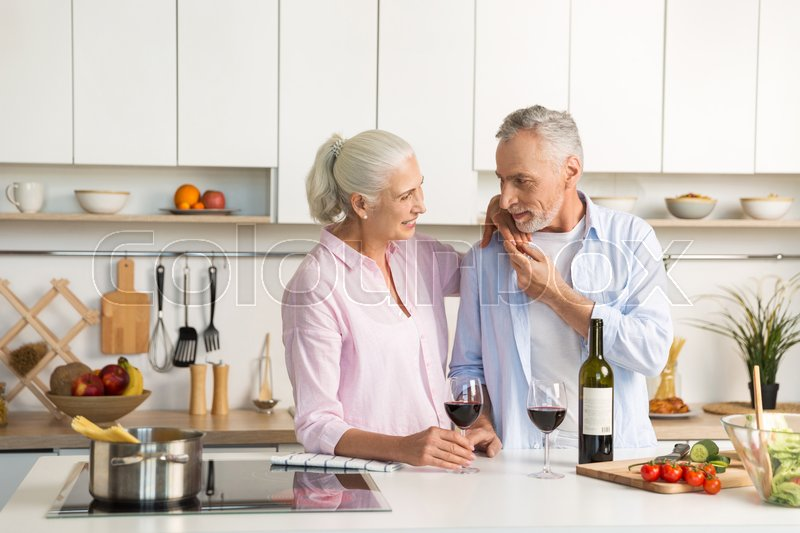 Stock image of 'Image of mature happy loving couple family standing at the kitchen drinking wine. Looking aside.'