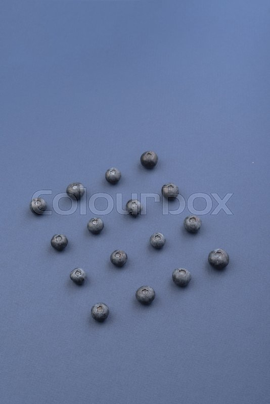 Stock image of 'Photo of blueberries isolated over blue background table.'