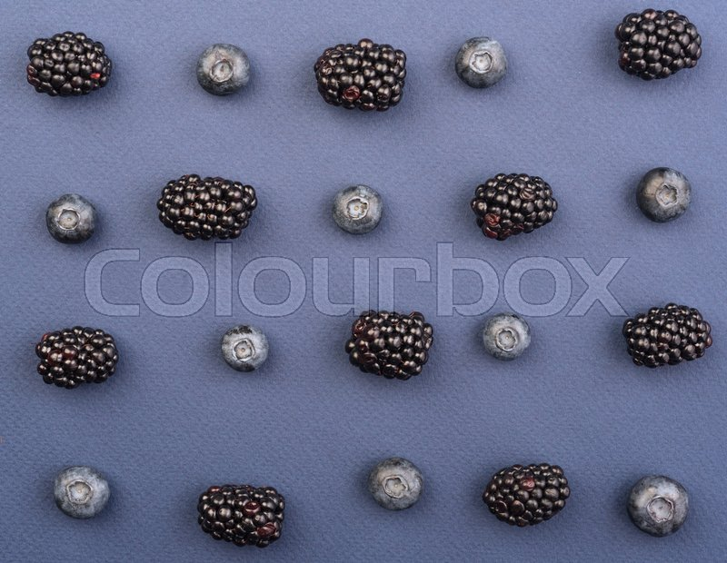 Stock image of 'Picture of mix of blueberries and mulberries isolated over blue background table.'