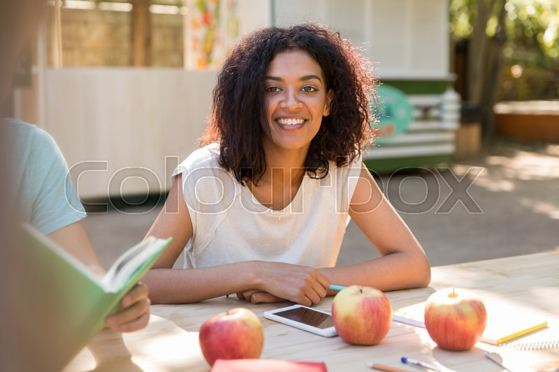Stock image of 'Picture of smiling young african lady sitting at the table near friends outdoors. Looking at camera.'