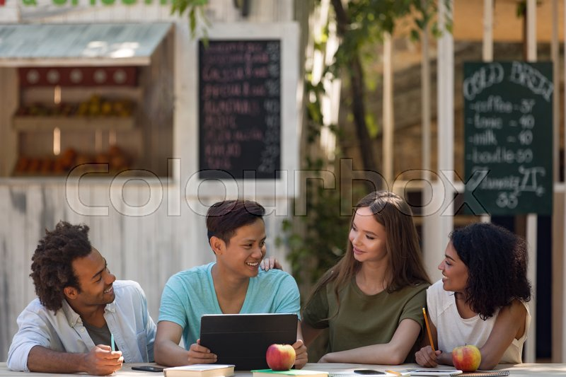 Stock image of 'Photo of smiling young multiethnic friends students outdoors using tablet computer and talking with each other. Looking aside.'