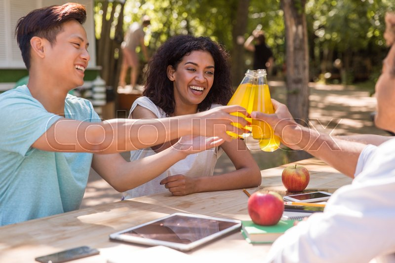 Stock image of 'Picture of cheerful young multiethnic friends students outdoors drinking juice and talking with each other. Looking aside.'