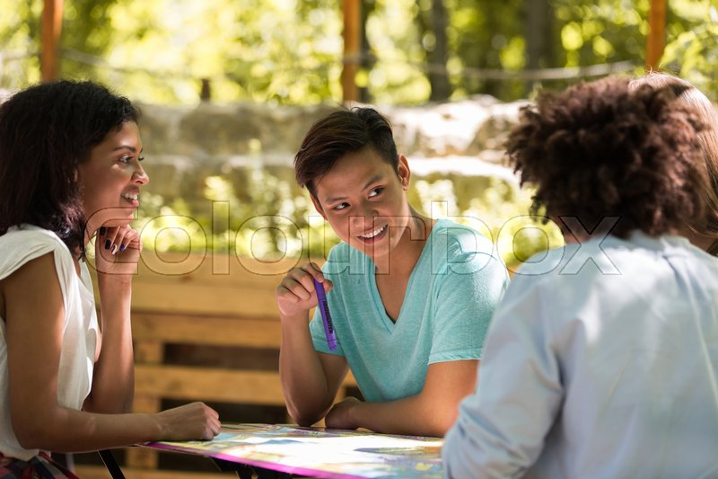 Stock image of 'Image of concentrated young multiethnic friends students outdoors studying and talking with each other. Looking aside.'