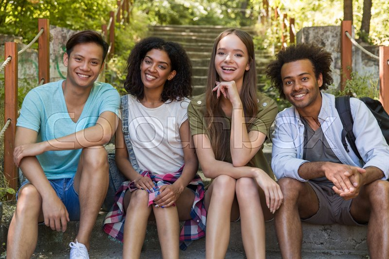 Stock image of 'Picture of young cheerful multiethnic friends students outdoors sitting on ladder. Looking camera.'