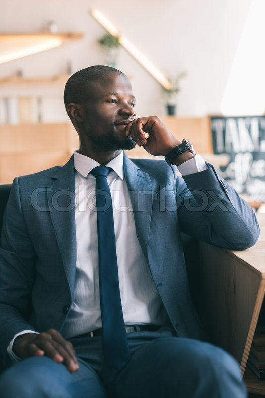 Stock image of 'handsome thoughtful african american businessman sitting in cafe '