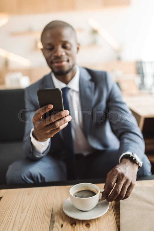 Stock image of 'handsome african american businessman using smartphone during coffee break in cafe '