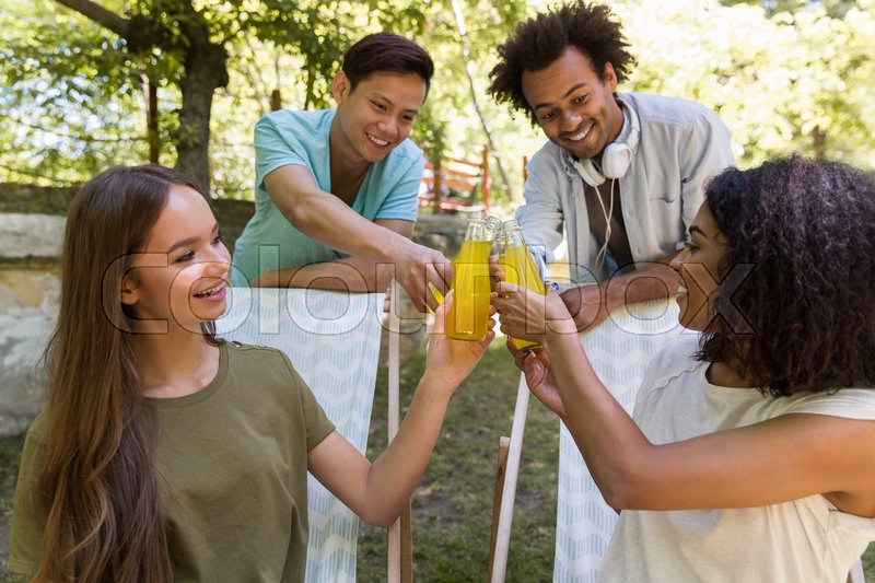 Stock image of 'Image of happy young multiethnic friends students outdoors drinking juice and talking with each other. Looking aside.'