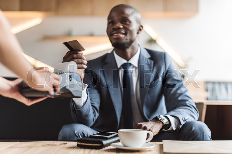 Stock image of 'handsome smiling african american businessman paying with credit card in cafe '