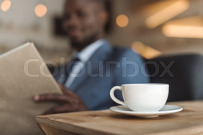 Stock image of 'Selective focus of handsome african american businessman reading menu in cafe, cup of coffee on foreground'