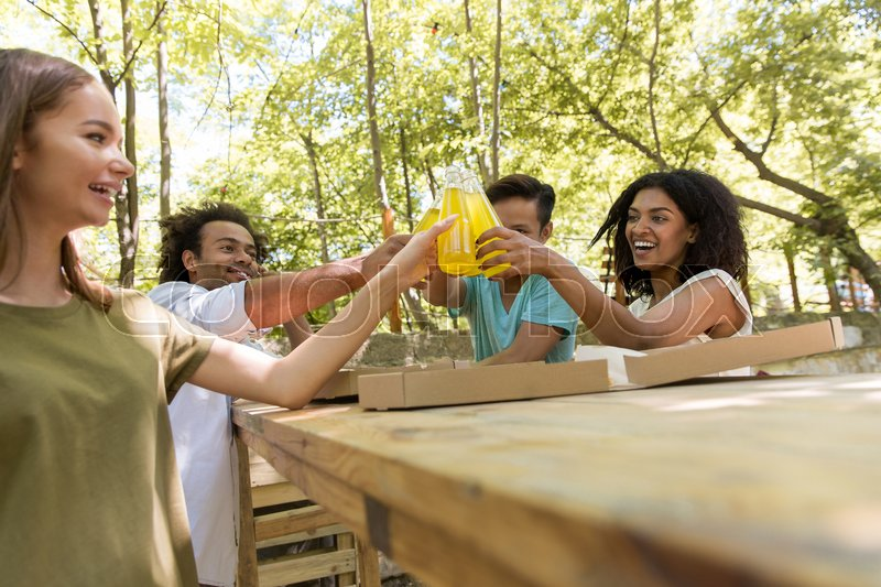 Stock image of 'Image of cheerful young multiethnic friends students outdoors drinking juice eating pizza and talking with each other. Looking aside.'