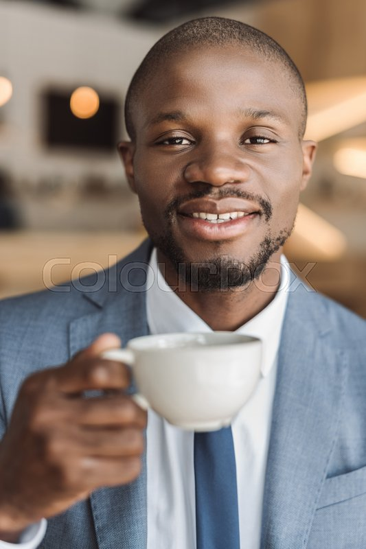 Stock image of 'handsome smiling african american businessman drinking coffee in cafe '