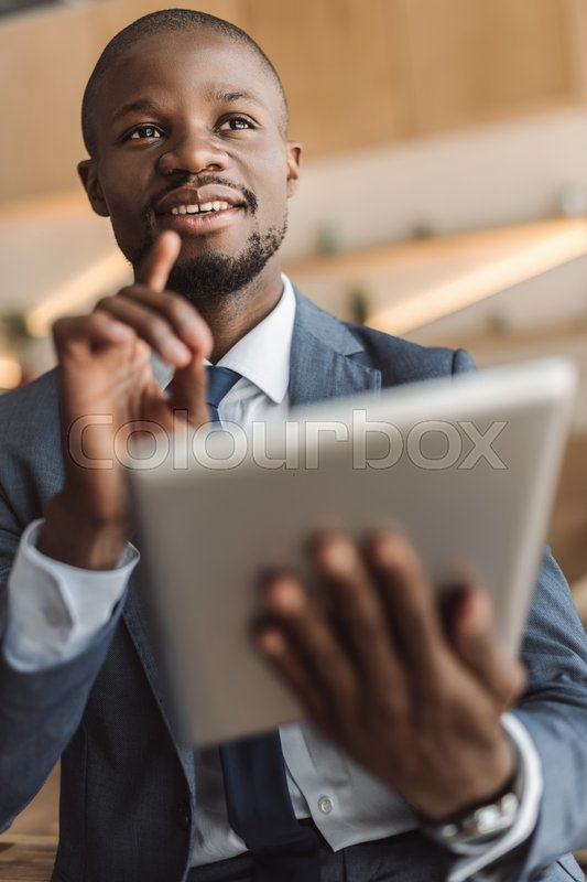 Stock image of 'handsome african american businessman having idea while working with digital tablet  '