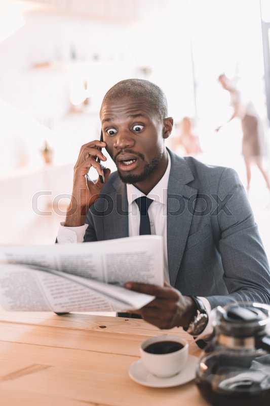 Stock image of 'shocked handsome african american businessman with smartphone reading newspaper during coffee break in cafe '