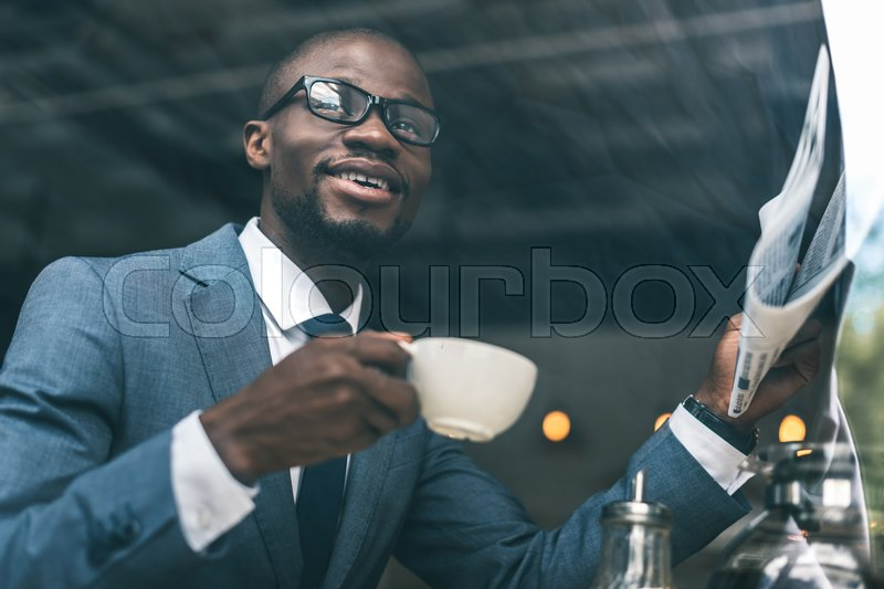 Stock image of 'Smiling handsome african american businessman with coffee cup reading newspaper in cafe'