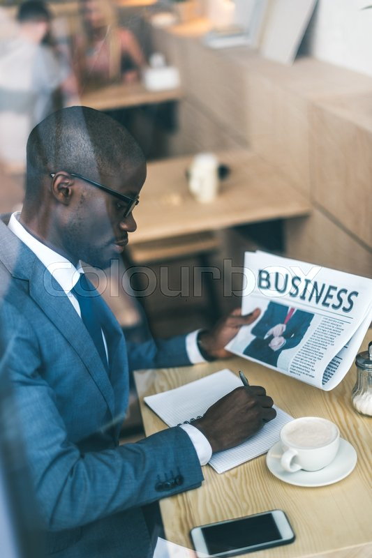 Stock image of 'Serious handsome african american businessman with newspaper working in coffee shop'