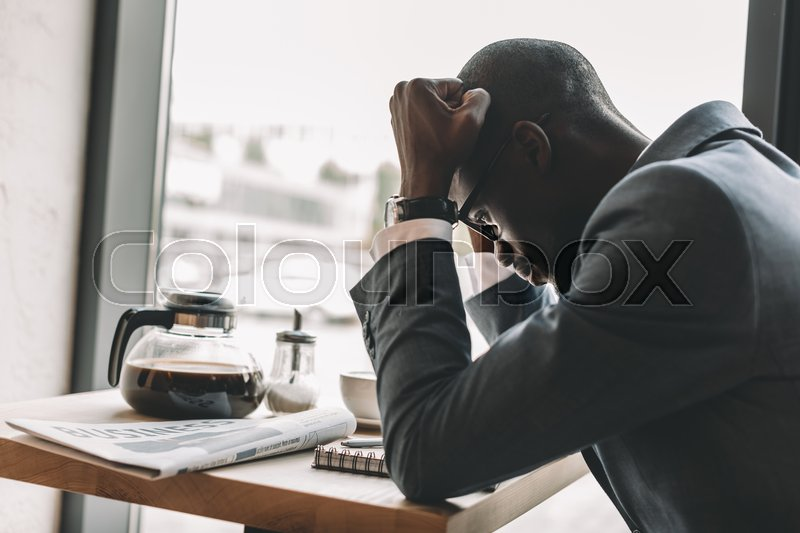 Stock image of 'Upset african american businessman working while sitting in coffee shop'