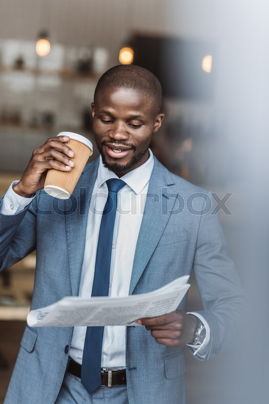 Stock image of 'Handsome african american businessman holding disposable coffee cup and reading newspaper'