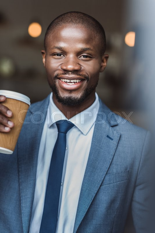 Stock image of 'Smiling handsome african american businessman holding disposable coffee cup'