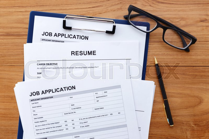 Stock image of 'Job application and resume on wood desk background'