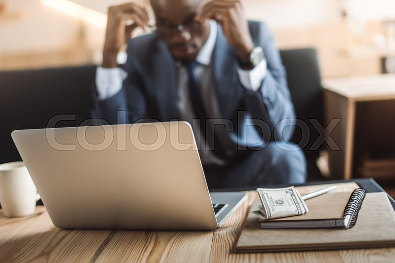 Stock image of 'tired african american businessman working with laptop and notepads in cafe '