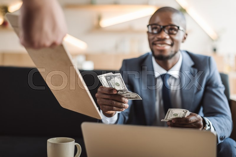 Stock image of 'Handsome african american businessman paying with cash in cafe'