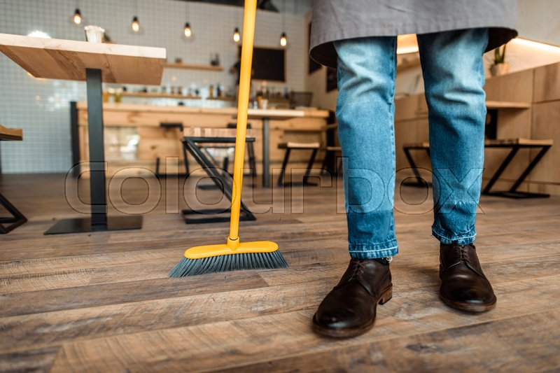 Stock image of 'Cropped view of african american worker sweeping with broom in coffee shop'