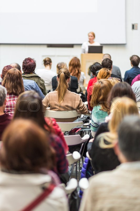 Stock image of 'Female speaker giving presentation in lecture hall at university workshop. Audience in conference hall. Rear view of unrecognized participant in audience. Scientific conference event.'