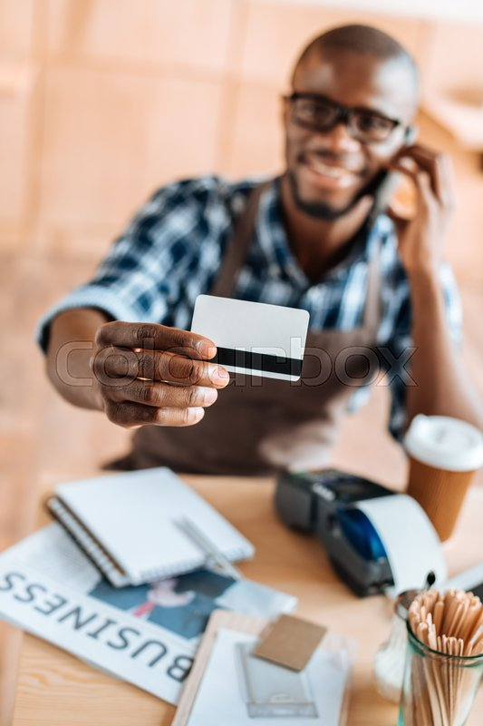Stock image of 'Selective focus of african american man showing credit card in coffee shop'