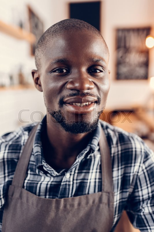 Stock image of 'Portrait of handsome african american male barista looking at camera'